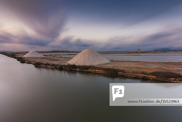 Salt pans with rows of tanks and two fully functional windmills on the coast connecting Marsala to Trapani  Trapani province Sicily Italy.