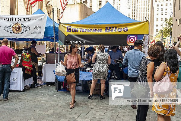 Tourists and office workers flock to Burmese Bites in The Outpost of the Queens Night Market  located in Rockefeller Plaza in New York on Tuesday  July 30  2019. The marketplace features ethnic and artisanal foods by small entrepreneurs all of whom are regulars at the Queens Night Market. Nine vendors will encamp in the plaza Monday through Thursday for three weeks. (© Richard B. Levine).
