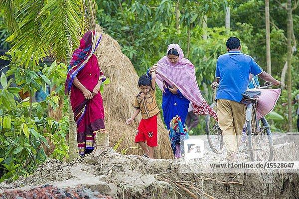 Bangladesh - June 27  2015: Man woman and peoples are crossing river erosion affected roadside at Rasulpur  Barisal District.