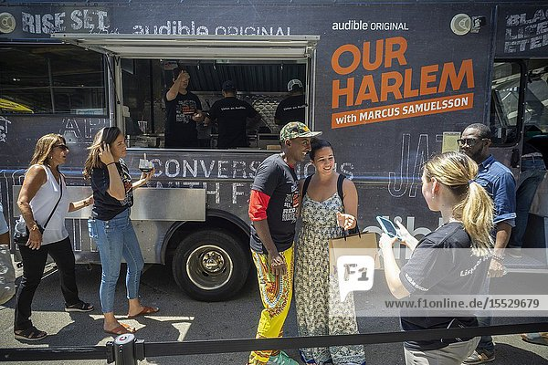 Celebrity Chef Marcus Samuelsson greets visitors to the Audible food truck serving samples of his dishes in Union Square in New York on Thursday  June 27  2019. Samuelsson voices Audibleâ.s audiobook adaptation  â. œOur Harlemâ.  of his Red Rooster Cookbook adding interviews. (© Richard B. Levine).