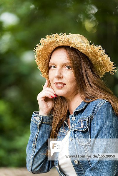 40 year old redheaded woman wearing a straw hat and a jean jacket looking at the camera  outdoors.