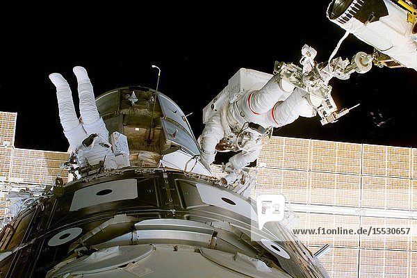 Astronauts James H. Newman (left) and Jerry L. Ross work between Zarya and Unity (foreground) during the first of three scheduled spacewalks on the STS-88 mission. Newman is tethered to the module  while Ross is anchored at the feet to a mobile foot restraint mounted on the end of the remote manipulator system (RMS) arm.