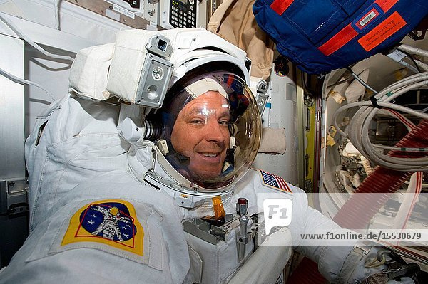 Air Force colonel and NASA astronaut Jack 2Fish Fischer is suited up in a U.S. spacesuit inside the crew lock portion of the U.S. Quest airlock preparing to exit the International Space Station on a contigency spacewalk.
