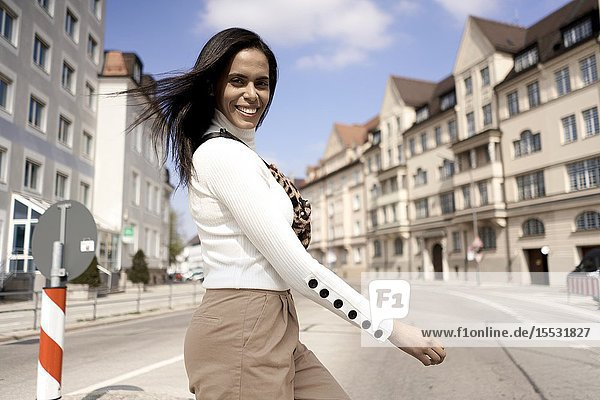 Happy Brazilian woman crossing the street  Munich  Germany