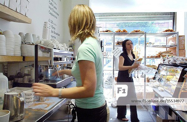 Two members of staff behind the counter serving coffee and bread at Euphorium Bakery in Islington  London