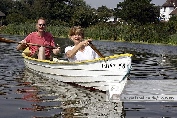 Couple paddling in a canoe on the lake at Thorpness  Suffolk