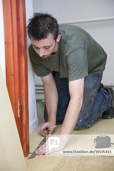 Carpet fitter laying a carpet