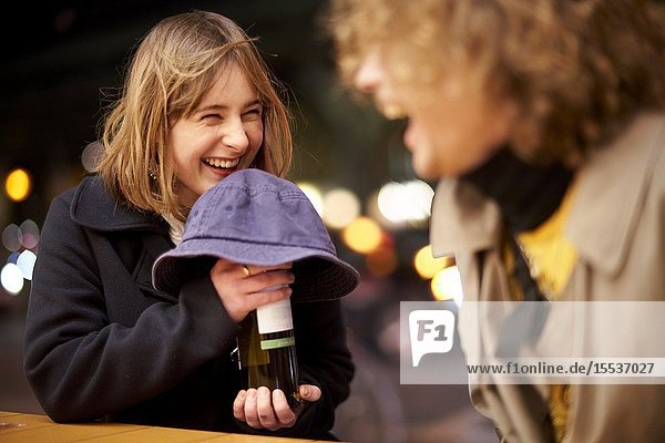 Happy woman hiding bottle of wine alcohol under hat at night  thrill of anticipation  nightlife in Berlin  Germany