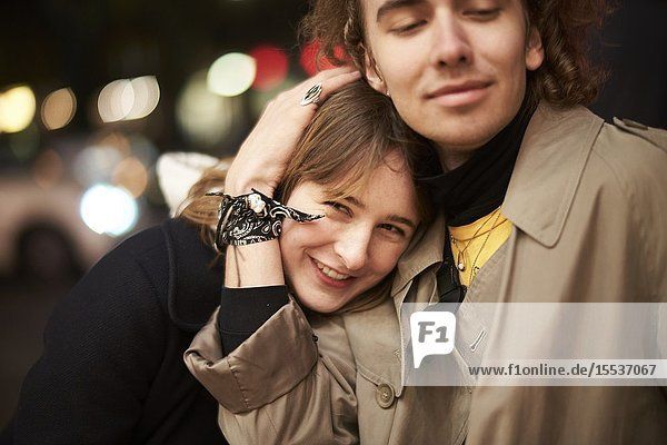 Woman and man embracing at street in city at night  in Berlin  Germany.