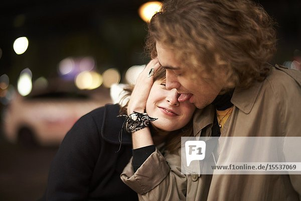Man licking face of woman at night  in Berlin  Germany.