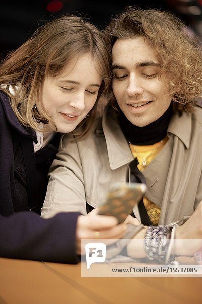 Couple looking at smartphone at night