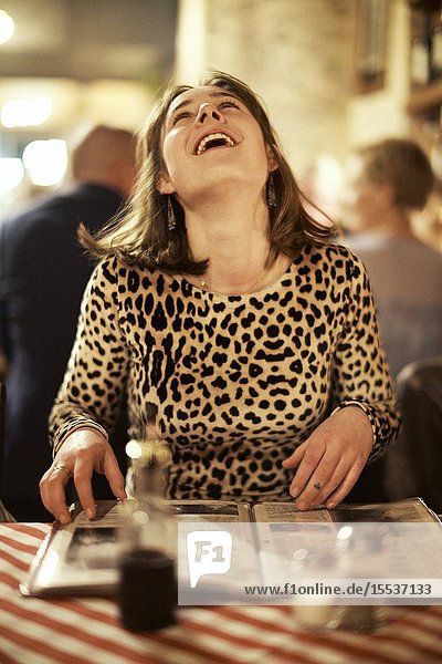 Woman laughing inside restaurant