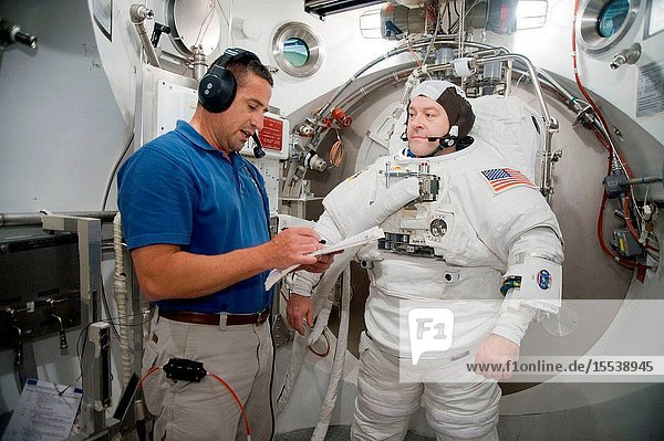 Astronaut Nicholas Patrick  STS-130 mission specialist  participates in an Extravehicular Mobility Unit (EMU) spacesuit fit check in the Space Station Airlock Test Article (SSATA) in the Crew Systems Laboratory at NASA's Johnson Space Center. Astronaut George Zamka  commander  assisted Patrick.