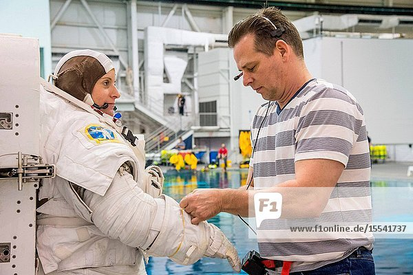 NASA astronaut Kathleen Rubins gets help donning a training version of her Extravehicular Mobility Unit (EMU) spacesuit in preparation for a spacewalk training session in the waters of the Neutral Buoyancy Laboratory (NBL) near NASA's Johnson Space Center.