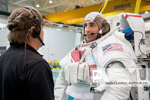 NASA astronaut Chris Cassidy  Expedition 3536 flight engineer  attired in a training version of his Extravehicular Mobility Unit (EMU) spacesuit  is pictured with a crew instructor during final preparations for a spacewalk training session in the waters of the Neutral Buoyancy Laboratory (NBL) near NASA's Johnson Space Center.