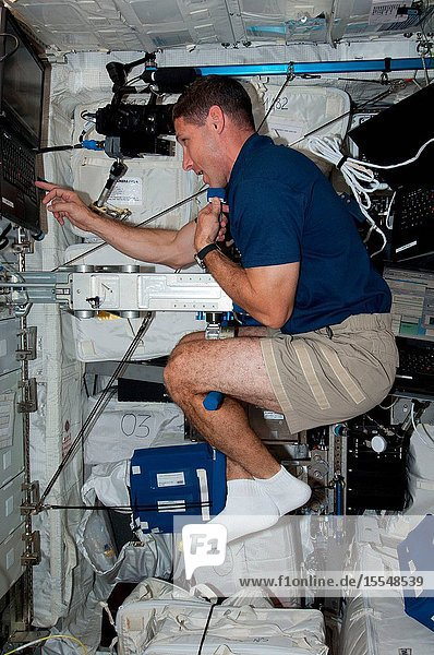 NASA astronaut Michael Hopkins  Expedition 37 flight engineer  performs Body Mass Measurement activities using the Space Linear Acceleration Mass Measurement Device (SLAMMD) in the Columbus laboratory aboard the Earth-orbiting International Space Station.