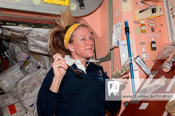 NASA astronaut Karen Nyberg  Expedition 37 flight engineer  prepares to eat a snack in the Unity node of the International Space Station.