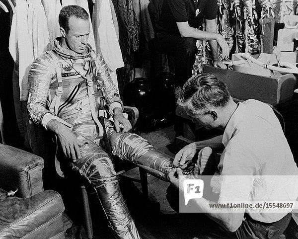 Mercury astronaut M. Scott Carpenter  prime pilot for the Mercury-Atlas 7 (MA-7) spaceflight  and Crew Equipment Specialist Joe Schmidt are pictured during a suiting exercise. Schmidt is seen lacing up Carpenter's boots.