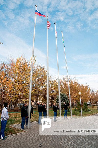 Outside their Cosmonaut Hotel crew quarters in Baikonur  Kazakhstan  the Expedition 3839 prime and backup crew members participate in the traditional flag-raising ceremony Oct. 27 as they conduct final pre-launch preparations. From left to right  prime Soyuz Commander Mikhail Tyurin and backup Max Suraev raise the Russian flag  prime Flight Engineer Rick Mastracchio of NASA and backup Reid Wiseman of NASA raise the U.S. flag  prime Flight Engineer Koichi Wakata of the Japan Aerospace Exploration Agency raises the Japanese flag and backup Flight Engineer Alexander Gerst of the European Space Agency raises the flag of Kazakhstan. Wakata  Tyurin and Mastracchio are scheduled to launch Nov. 7  Kazakh time  in the Soyuz TMA-11M spacecraft from Baikonur to begin a six-month mission on the International Space Station.Victor Zelentsov