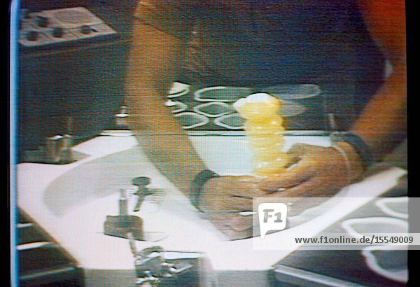 An accordian-style beverage dispenser filled with orange juice is held by astronaut Charles Conrad Jr.  Skylab 2 commander  in this close-up view which is a reproduction taken from a color television transmission made by a TV camera aboard the Skylab 1 2 space station cluster in Earth orbit. Conrad (head and face not in view) is seated at the wardroom table in the crew quarters of the Orbital Workshop. The dispenser contained beverage crystals  and Conrad has just added the prescribed amount of water to make the orange drink.