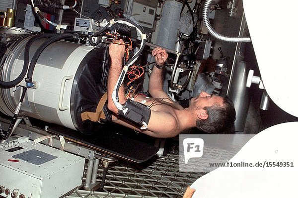 Scientist-astronaut Owen K. Garriott  science pilot of the Skylab 3 mission  lies in the Lower Body Negative Pressure Device in the work and experiments area of the Orbital Workshop (OWS) crew quarters of the Skylab space station cluster in Earth orbit. This picture was taken with a hand-held 35mm Nikon camera. Astronauts Garriott  Alan L. Bean and Jack R. Lousma remained with the Skylab space station in orbit for 59 days conducting numerous medical  scientific and technological experiments. The LBNPD (MO92) Experiment is to provide information concerning the time course of cardiovascular adaptation during flight  and to provide in-flight data for predicting the degree of orthostatic intolerance and impairment of physical capacity to be expected upon return to Earth environment. The bicycle ergometer is in the right foreground.