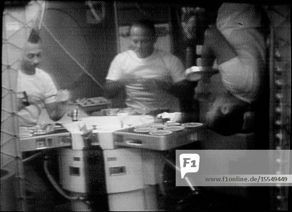 The three Skylab 3 crewmen are shown eating in the Orbital Workshop (OWS) wardroom of the Skylab space station in Earth orbit  in this photographic reproduction taken from a television transmission made by a color TV camera aboard the OWS. Astronaut Alan L. Bean (right)  commander  illustrates eating under zero-gravity conditions upsidedown. The two other crewmen are scientist-astronaut Owen K. Garriott (left)  science pilot  and astronaut Jack R. Lousma  pilot.