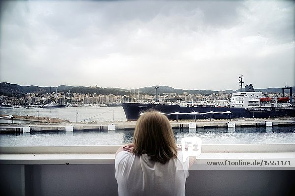 Back view of woman with on the deck of a boat looking at the port and the city. Palma de Mallorca  Baleares  Spain  Europe.