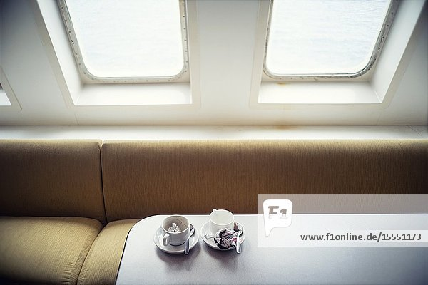 Two empty coffee cups on the dining table of a boat. Mediterranean Sea  Spain  Europe.