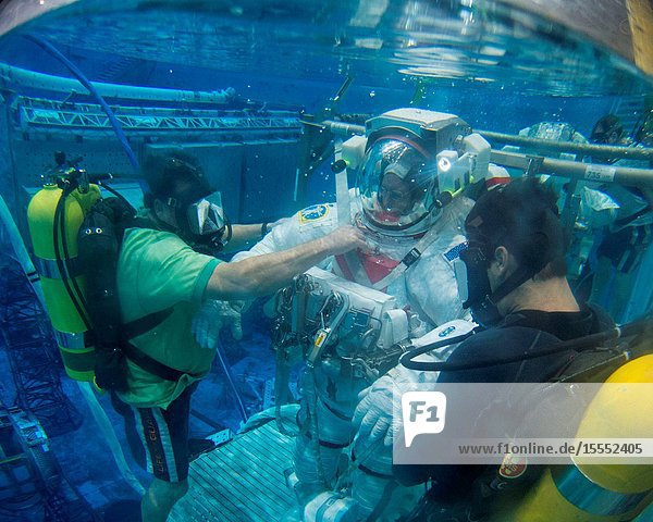 A fisheye lens was used to capture this image of NASA astronaut Barry Wilmore  Expedition 41 flight engineer and Expedition 42 commander  attired in a training version of his Extravehicular Mobility Unit (EMU) spacesuit  as he is submerged in the waters of the Neutral Buoyancy Laboratory (NBL) near NASA's Johnson Space Center. Divers are in the water to assist Wilmore in his rehearsal  which is intended to help prepare him for possible work on the exterior of the International Space Station.