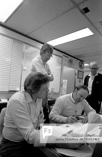 Mission evaluation room (MER) team members discuss 51-L in the Johnson Space Center's engineering office facility. Left to right are Charles Walsh  Larry Meyers  David Camp and Travis Libby.