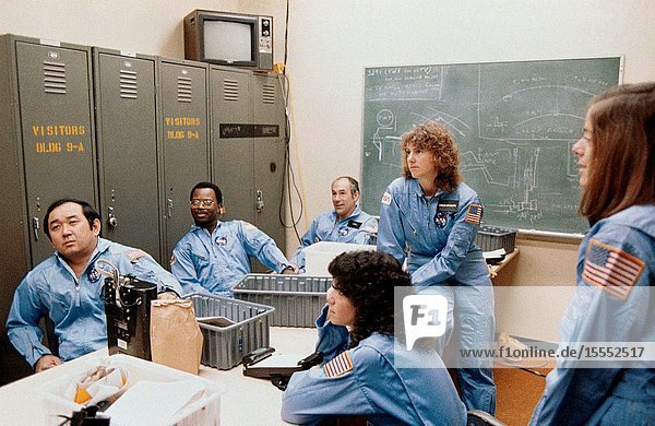 Five members of the prime crew for NASA's STS-51L mission and a backup crew member are briefed during a training session in the Johnson Space Center's (JSC) Shuttle Mock-up and Integration Laboratory. From left to right are astronaut Ellison S. Onizuka  mission specialist  Ronald E. McNair  mission specialist  Gregory D. Jarvis  Hughes payload specialist  Judith A. Resnik  mission specialist  Sharon Christa McAuliffe  citizen observerpayload specialist representing the Teacher-in-Space Project  and Barbara R. Morgan  backup payload specialist. The photograph was taken by Keith Meyers of the New York Times.