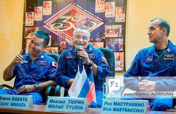 Expedition 38 Soyuz Commander Mikhail Tyurin of Roscosmos  center  talks as Flight Engineer Koichi Wakata of the Japan Aerospace Exploration Agency  left  and Flight Engineer Rick Mastracchio of NASA listen  while quarantine behind glass  during the final press conference held a day ahead of their launch to the International Space Station  Nov. 6  2013 at the Cosmonaut Hotel in Baikonur  Kazakhstan.