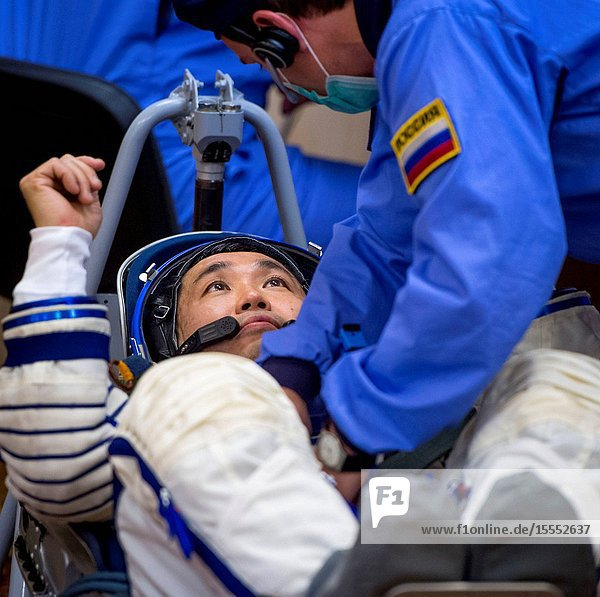 Expedition 38 Flight Engineer Koichi Wakata of the Japan Aerospace Exploration Agency is seen through glass as he and fellow crew mates  Soyuz Commander Mikhail Tyurin of Roscosmos and Flight Engineer Rick Mastracchio of NASA  have their Russian Sokol suits pressure checked a few hours ahead of their launch  Nov. 7  2013  in Baikonur  Kazakhstan. Tyurin  Wakata and Mastracchio will launch in their Soyuz TMA-11M spacecraft to the International Space Station to begin a six-month mission.
