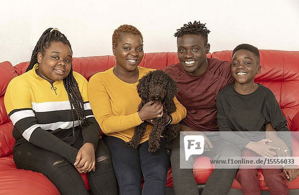 Hampshire  UK. circa 2019. Family portrait with a black Poddle pet dog