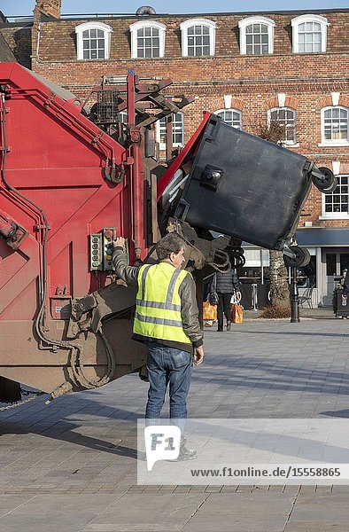 Salisbury  Wiltshire  England  UK. February 2019. Operative loading a commercial size red refuse bin into a truck in the city centre.