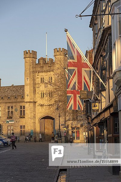 Wells  Somerset  England  UK. March 2019. Glowing sun illuminates the Market Place and Bishops Eye Gatehouse in the cathedral city in the Mendip district of Somerset.