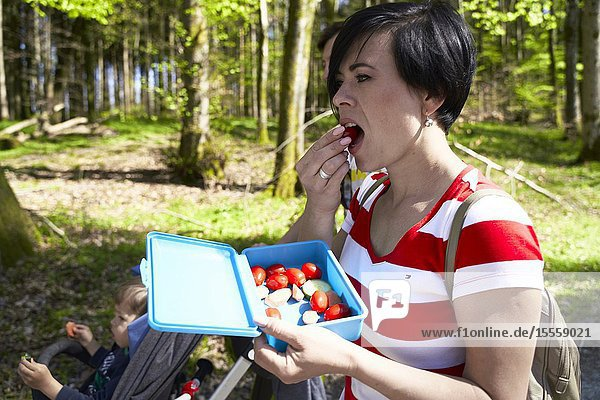 Woman eating tomato while walking with family in forest  at Herrenchiemsee  Chiemsee  Bavaria  Germany
