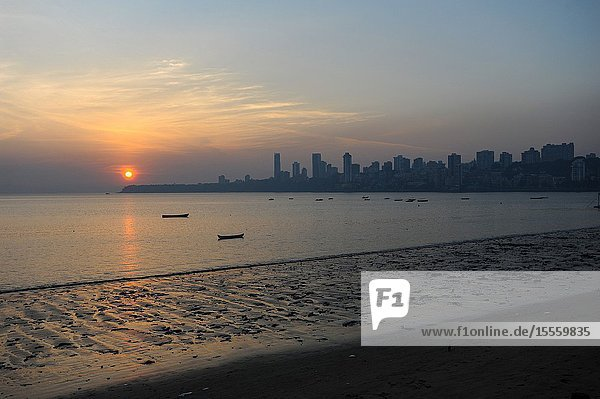 Mumbai  Maharashtra  India  Asia - Sunset on Chowpatty Beach along Marine Drive with the silhouette of the Malabar Hill city skyline in the backdrop.