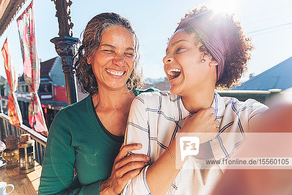 Selfie point of view laughing  happy mother and daughter on sunny balcony