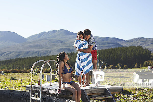 Happy  affectionate family at remote  sunny  summer poolside