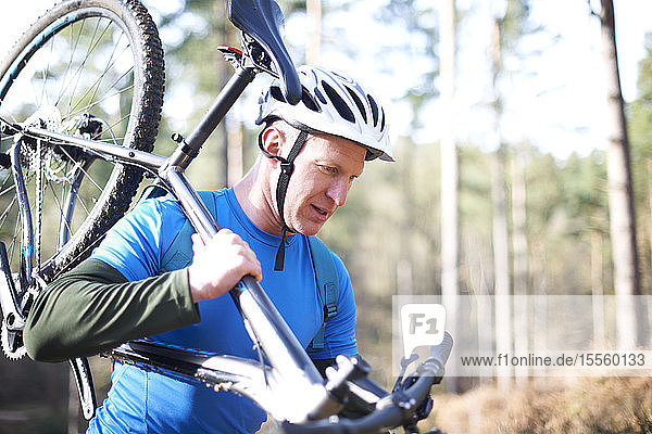 Male cyclist carrying bicycle in sunny woods