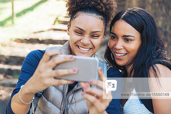 Happy young women friends taking selfie with smart phone