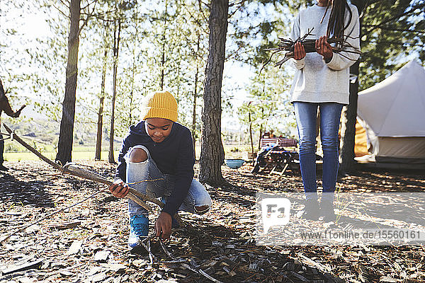 Boy picking up sticks for firewood at sunny campsite in woods