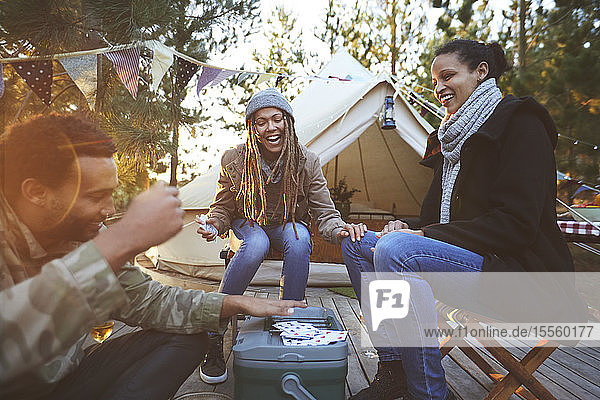 Happy friends playing cards at campsite