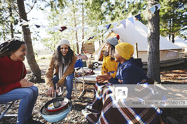 Lesbian couple and kids cooking breakfast at campsite grill in woods