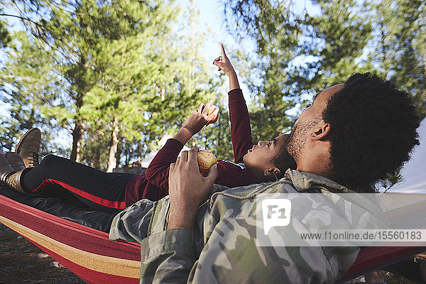 Father and son relaxing in hammock below trees in woods