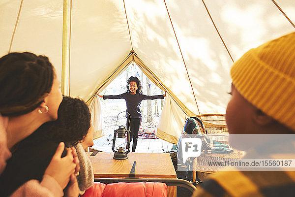 Family watching happy girl enter camping yurt