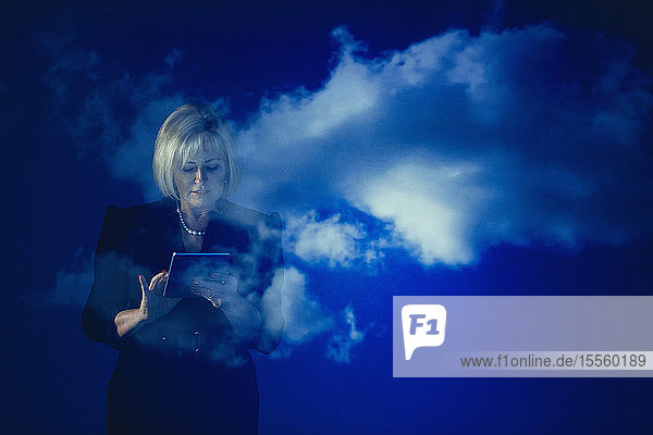 Double exposure businesswoman with digital tablet against blue sky with clouds