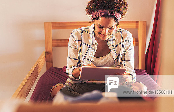 Young female college student using digital tablet on dorm room bunk bed