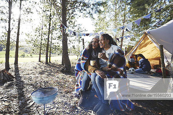 Happy lesbian couple relaxing  drinking coffee at sunny campsite in woods